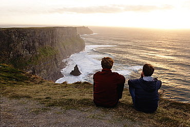 Two men sitting on The Cliffs of Moher, The Burren, County Clare, Ireland