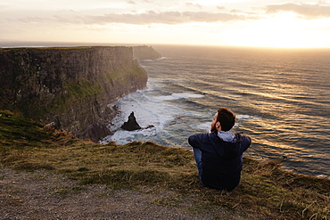 Mid adult man sitting on The Cliffs of Moher, The Burren, County Clare, Ireland