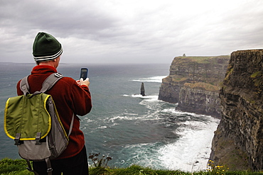 Mid adult man taking photo, Cliffs of Moher, The Burren, County Clare, Ireland