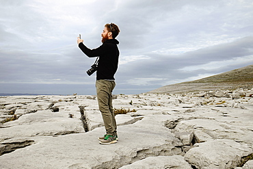 Mid adult man taking photo on phone, The Burren, County Clare, Ireland