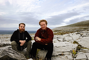 Two men sitting on rocks, The Burren, County Clare, Ireland