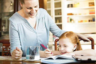 Mid adult mother helping daughter with school homework at dining room table