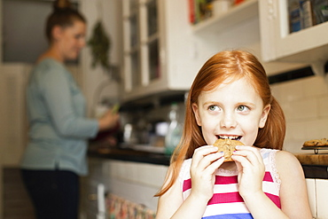 Girl eating biscuit in kitchen