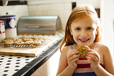 Portrait of girl eating biscuit in kitchen