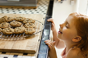 Girl peeking over kitchen counter at biscuits