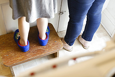 Legs of mid adult mother next to daughter standing on stool in kitchen