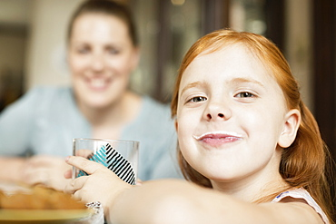 Girl with a milk moustache at dining room table