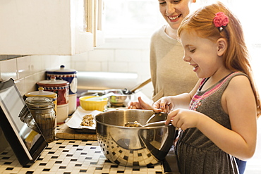 Girl and mid adult mother baking together in kitchen