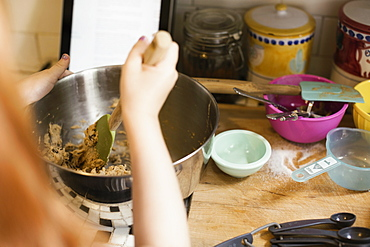 Over shoulder view of girls hand mixing in kitchen bowl