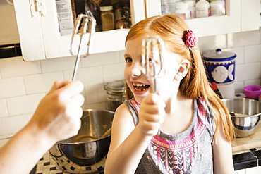 Girl and mother holding up whisks in kitchen