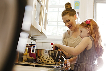 Mid adult mother giving daughter a helping hand in kitchen