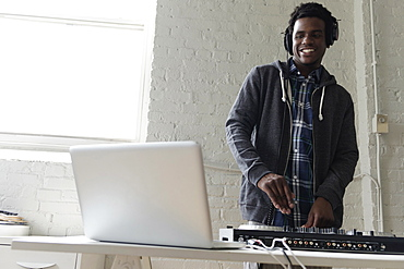 DJ using laptop and mixing desk