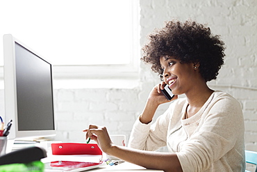 Young woman on smartphone at desk