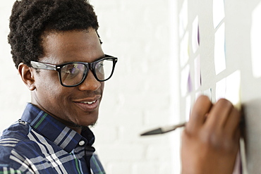 Young man wearing glasses writing on adhesive note