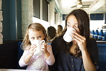 Mother and toddler drinking mugs of coffee in diner