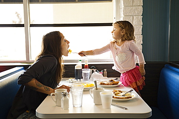 Toddler daughter feeding mother in diner