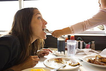 Toddler daughter feeding mother from fork in diner