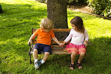 Male and female toddler friends holding hands on scaled park bench