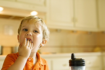 Male toddler eating with hands in kitchen