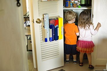 Male and female toddler friends searching pantry