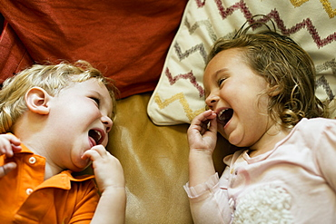 Male and female toddler friends giggling on sofa