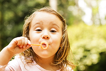 Close up portrait of female toddler blowing bubbles in garden