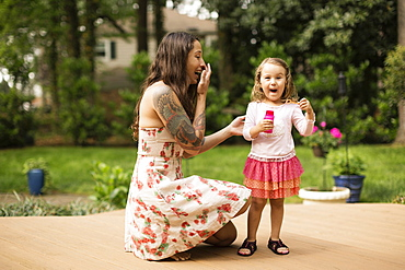 Mother and toddler daughter blowing bubbles in garden