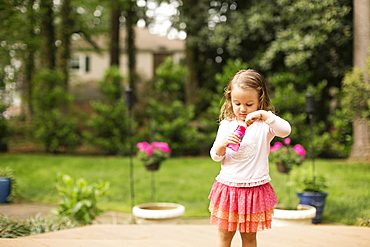Female toddler preparing to blow bubbles in garden