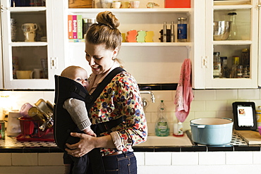 Mid adult mother with baby son in sling in kitchen