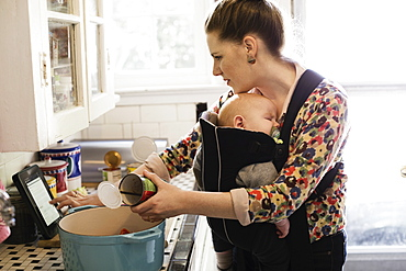 Mid adult mother with baby son in sling preparing food in kitchen