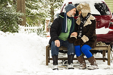 Mature couple sitting on toboggan in snow