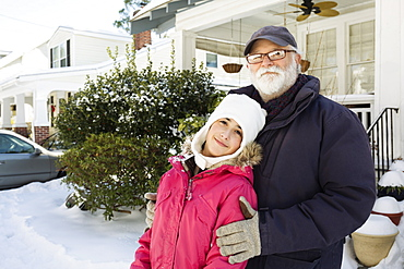 Grandfather and granddaughter outside house in winter