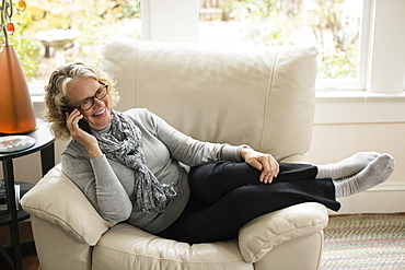 Relaxed senior woman sitting on chair talking on mobile