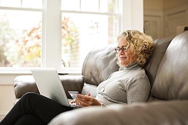 Senior woman shopping online on laptop