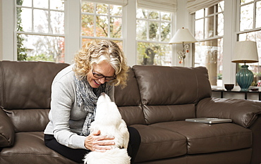 Senior woman with labrador dog in living room