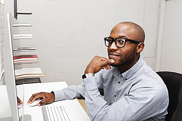Portrait of young man using computer in design office