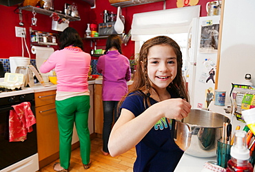 Girl in kitchen with mother and sister in background