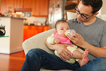Father sitting on sofa feeding baby daughter
