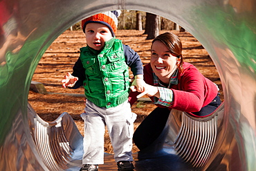 Mother helping son play on slide