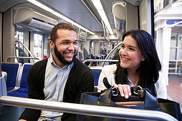 Young couple traveling on light train