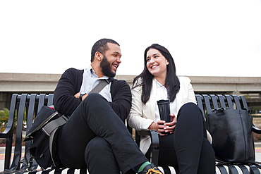Young couple sitting on bench on platform