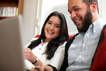 Young couple using laptop at home