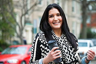Young woman carrying travel mug
