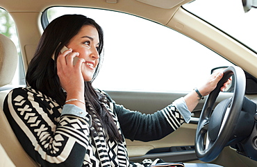 Young woman on cell phone driving car