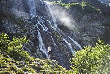 Russia, Karachay-Cherkessia, Arkhyz, Man standing near Sofiyskiye Vodopady waterfall in Caucasus Mountains