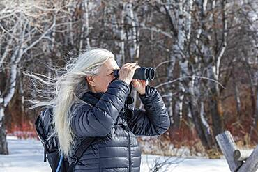 USA, Idaho, Bellevue, Senior woman using binoculars while hiking