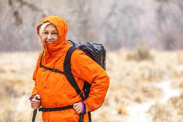 USA, Utah, Escalante, Woman hiking during snow flurry in Grand Staircase-Escalante National Monument