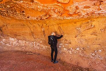 USA, Utah, Escalante, Woman touching sandstone cave wall in Grand Staircase-Escalante National Monument