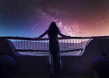 Dubai, United Arab Emirates, Woman in luxury resort in desert watching falling star at starry sky at night