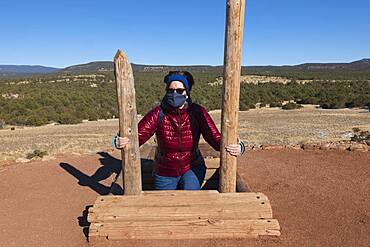 USA, New Mexico, Pecos, Woman in face mask climbing out of storage shelter at Pecos National Historical Park